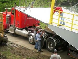 Brian Froedge and Joe Stephens unchain the new KY 214 ferry from the tractor trailer.