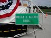 "A decorative ""William H. Natcher Bridge"" sign on display at the ceremony's stage."